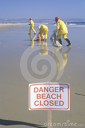 Workers remove oil from the California shoreline Editorial Image
