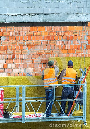 Free Workers Work On A Construction Site. Work Is Underway On The Laying Of Panels Of Wall Insulation From Red Brick. Royalty Free Stock Image - 129980056