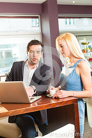 Working colleagues - a man and a woman - in cafe
