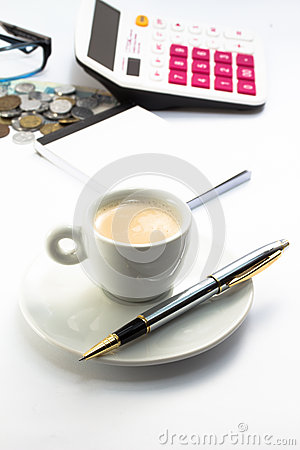 Working environment with calculator pen notebook and a cup of coffee