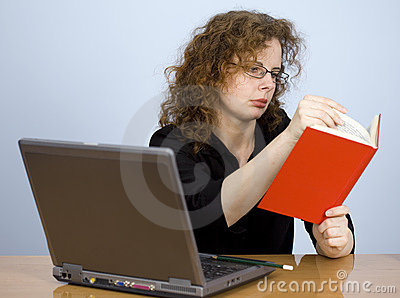 Working on laptop woman checks in red book