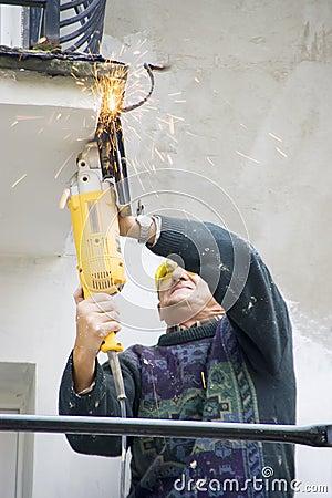 Workman with electric saw