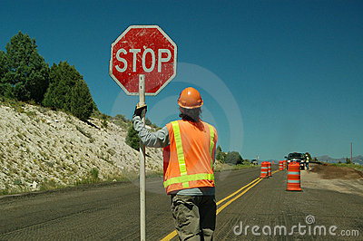 Workman holding stop sign
