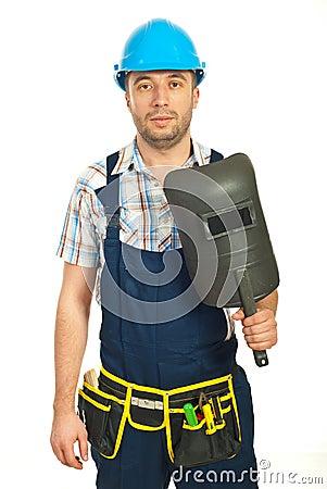 Workman holding welding mask