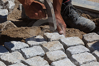 Workman laying cobbles