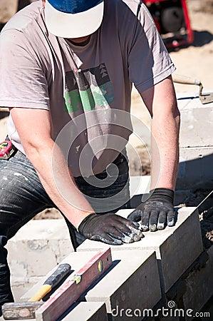 Workman laying concrete blocks