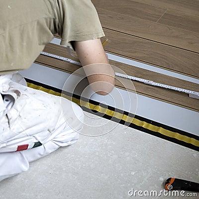 Workman laying flooring