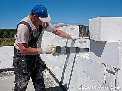 Workman sawing blocks
