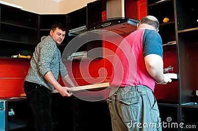 Workmen fitting kitchen