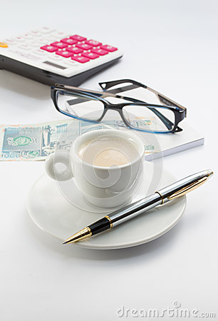 Workong environment white table or place with cup of coffee glasses pen calculator and money