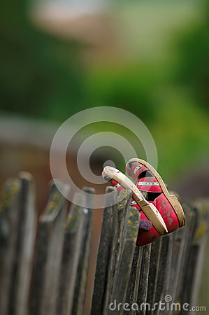 Worn kids shoes on fence