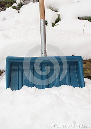 Worn snow shovel repaired with tape around handle