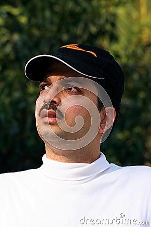 Worried Asian sportsman in cap