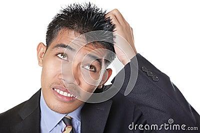 Worried businessman scratching head
