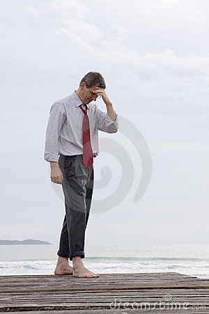 Worried businessman at the sea