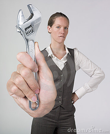 Worried businesswoman holding monkey wrench