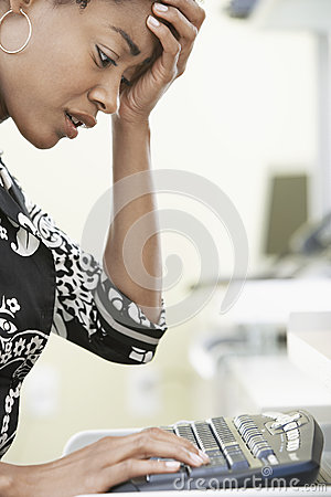 Worried Businesswoman Typing On Computer Keyboard