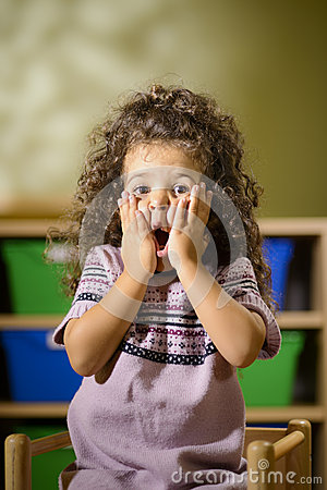 Worried child with mouth open in kindergarten