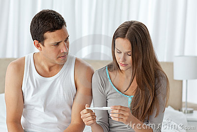 Worried couple looking at a pregnancy test