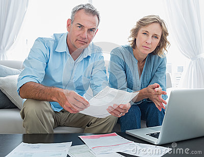 Worried couple paying their bills online with laptop looking at