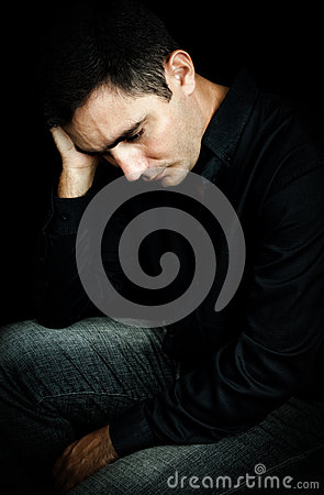 Worried and depressed man isolated on black
