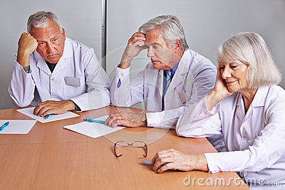 Worried doctors thinking in meeting