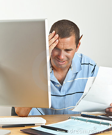Worried Man with Headache Paying Bills