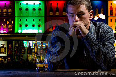 Worried man sitting at bar with whiskey glass. Dar