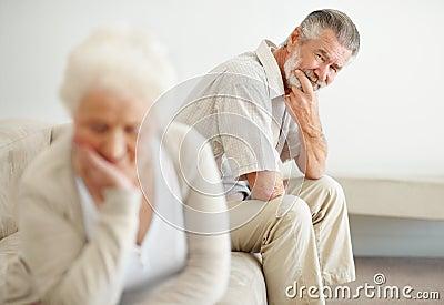 Worried mature man looking at a sad senior woman