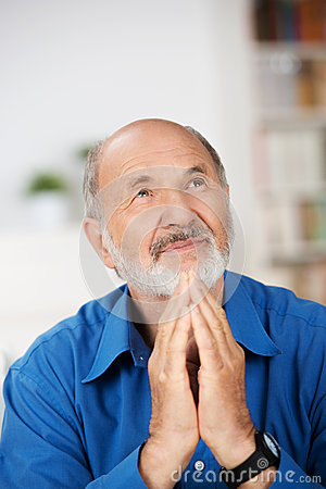 Worried religious senior man praying