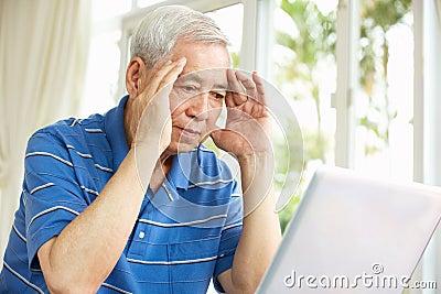 Worried Senior Chinese Man Using Laptop At Home