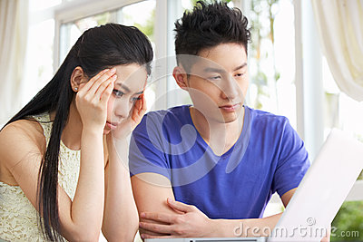 Worried Young Chinese Couple Using Laptop