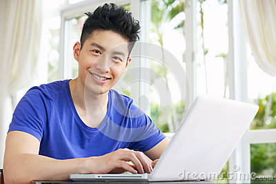Worried Young Chinese Man Using Laptop At Home