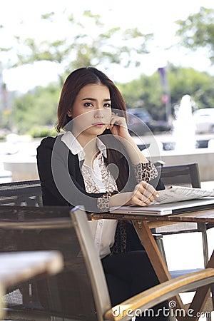 Worry Asian woman, newspaper bad news