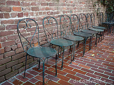 Wrought iron chairs lined up on a brick patio
