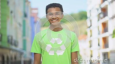 Wstydliwy, młody ekoochotnik w recyklingu sygnalizuje uśmiech na kamerze, oszczędność przyrody zdjęcie wideo