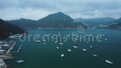 Yachts and boats parked in the sea bay, aerial view. Near the pier, boats on the shore. Away the mountains and the city. Beautiful landscape stock video footage