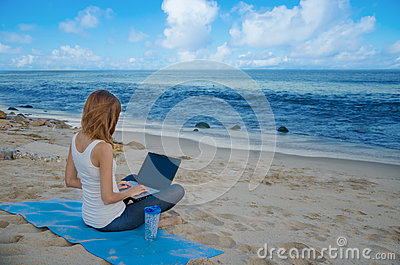 Yang woman with laptop by the ocean