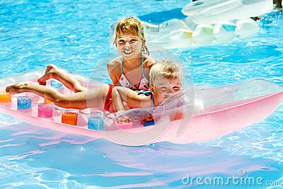 Children swimming on inflatable beach mattress.