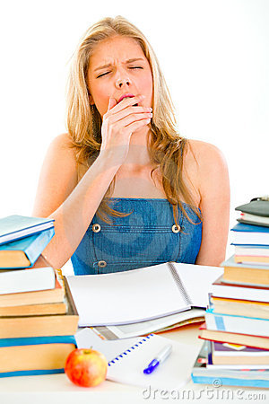 Yawning teen girl sitting at table with books