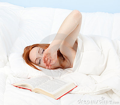Yawning woman relaxing with book in white bedding
