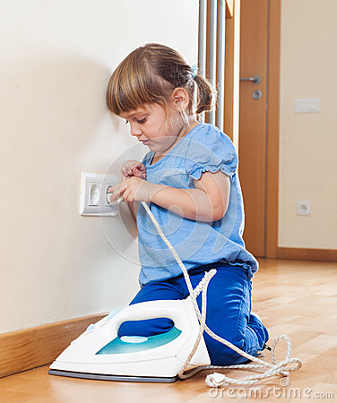 3 years girl playing with electric iron Stock Photo
