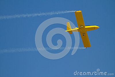 Yellow airplane speeds by with blue sky