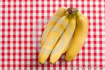 Yellow bananas on checkered tablecloth
