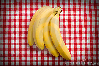 Yellow bananas on checkered tablecloth