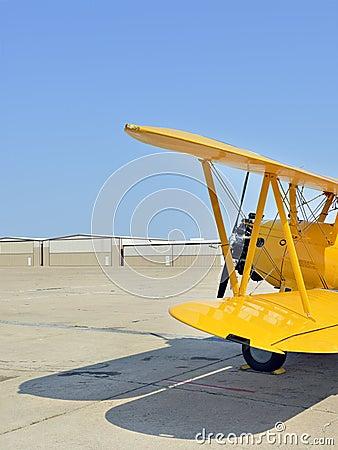 Yellow biplane at airfield