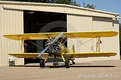 Yellow biplane in front of hangar