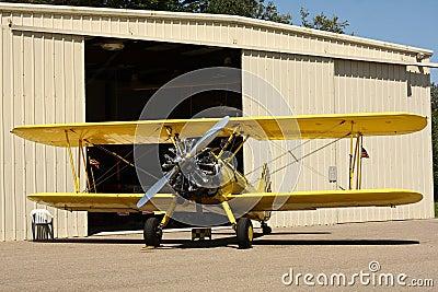 Yellow biplane in front of hangar