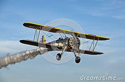 Yellow biplane with smoke.