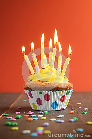 Yellow birthday cupcake full of candles